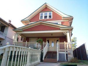 "This gable-roofed Prairie-style house has been ""Victorianized"" with turned stock balusters, porch brackets, a new door with oval light and a bright three-color paint scheme."